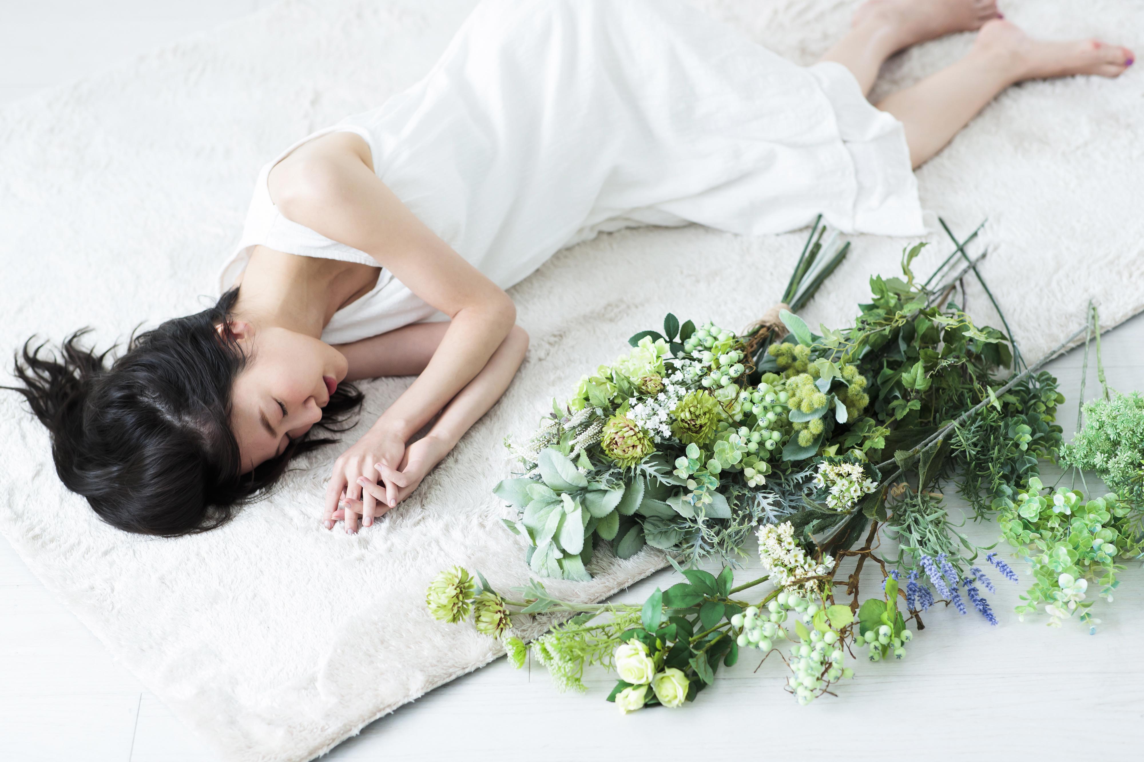 白いワンピースで横たわる女性