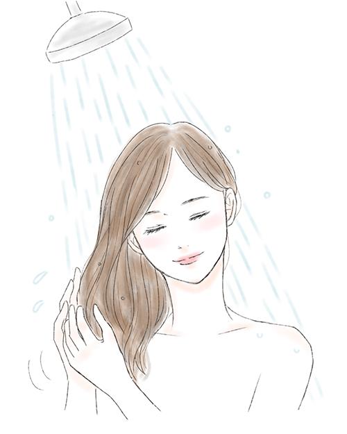 シャワーで髪を洗い流す女性