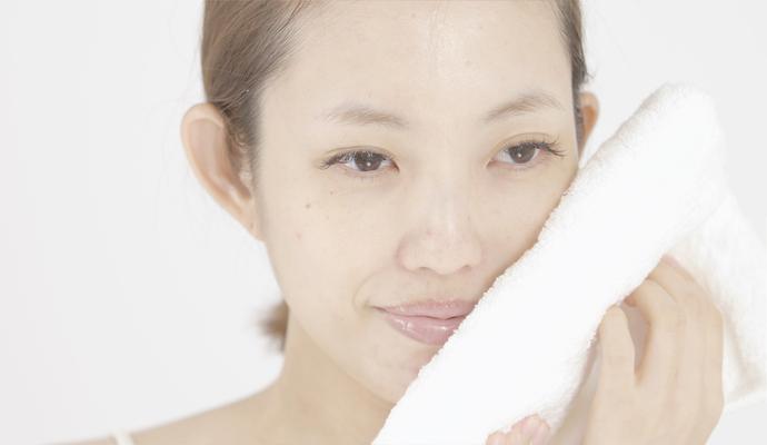 洗顔後、顔にやさしくタオルをあてている様子