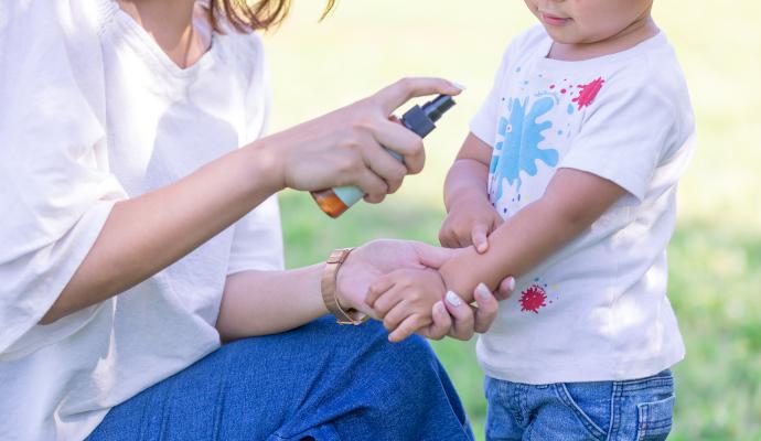 公園で子供の腕に虫除けスプレーをするママ