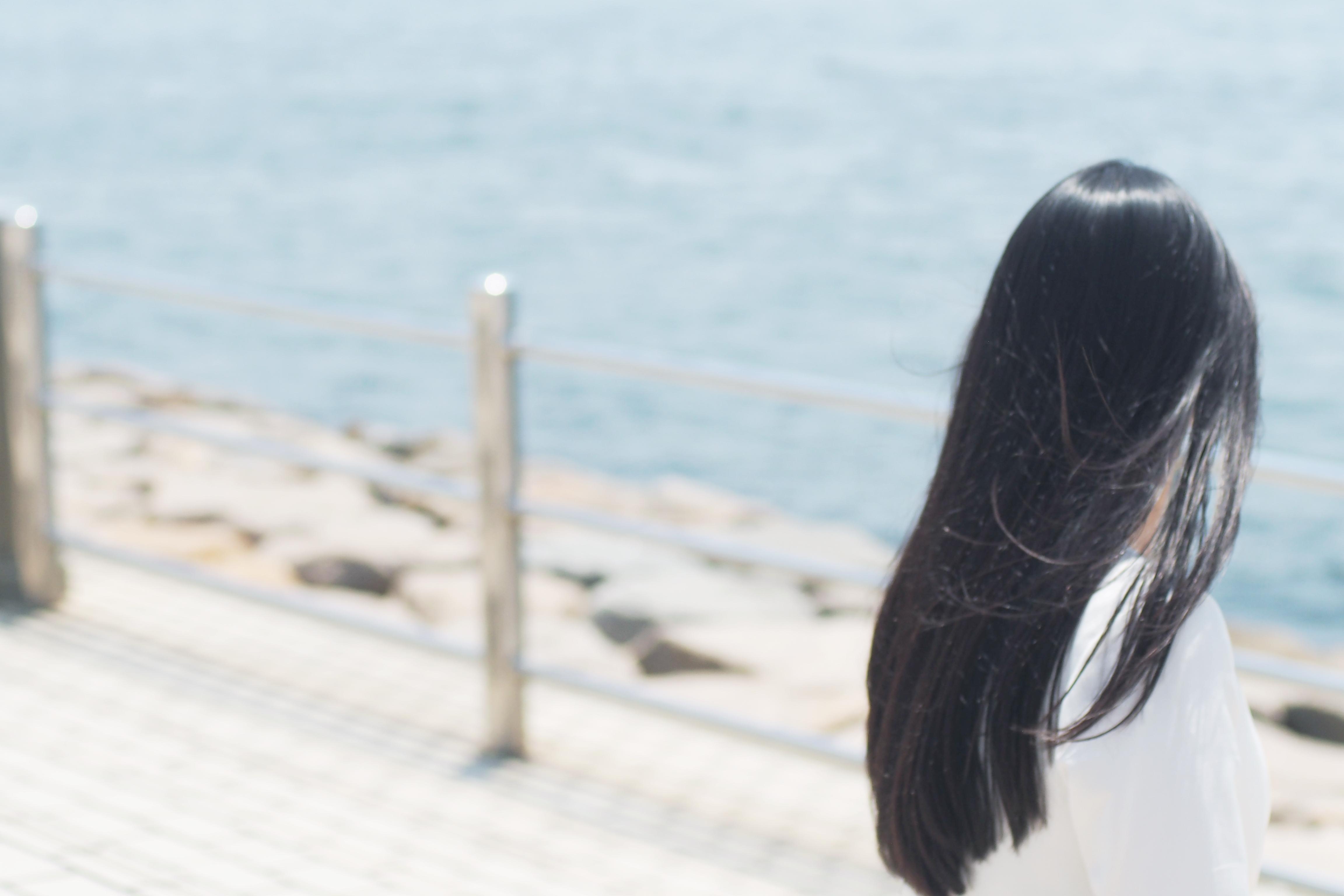 ロングヘアが風になびく黒髪の女性