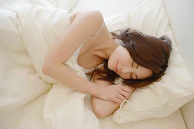 白いベッドで睡眠中の女性