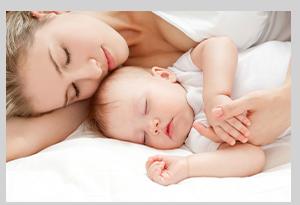 眠っている赤ちゃんとママの写真