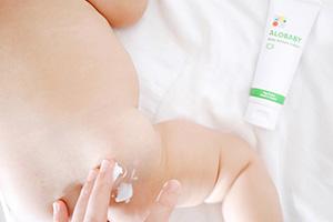 赤ちゃんにアロベビーべビークリームを塗っている様子