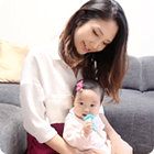 母親の膝の上で歯磨きをする赤ちゃんの写真